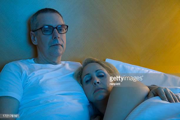 Pareja madura viendo televisión antes de irse a la cama
