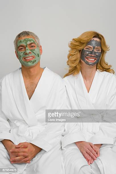 Mature couple wearing facial masks and sitting together