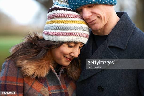 mature couple wearing knit hats hugging - 毛皮の飾り ストックフォトと画像