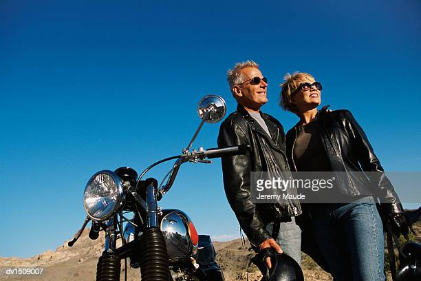 mature couple wearing leather jackets stand in the desert next to a motorbike, smiling - バイクヘルメット ストックフォトと画像