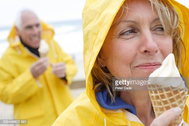 Mature couple wearing rain gear, eating ice cream at beach