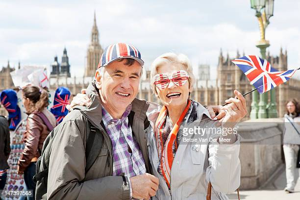 Mature couple wearing tourist glasses and hat.