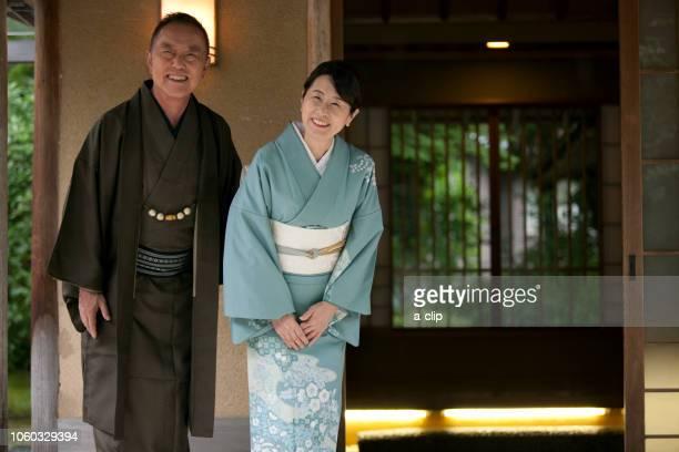 玄関で挨拶する中高年夫婦 - 旅館 ストックフォトと画像