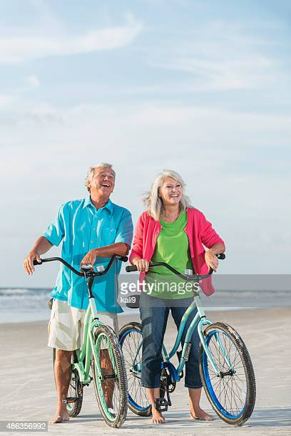 Mature couple with bicycles at the beach
