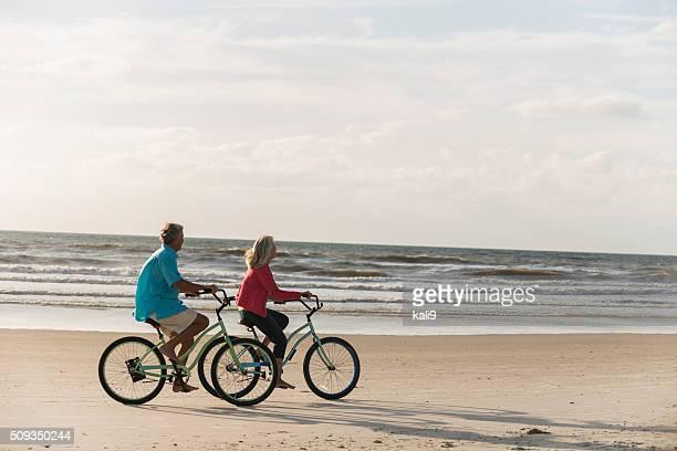 Älteres Paar mit Fahrrädern am Strand