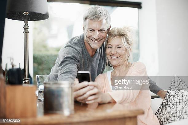 Mature couple with cell phone having fun