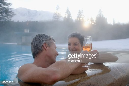 germany bavaria mature couple with champagne in hot tub smiling stock photo getty images. Black Bedroom Furniture Sets. Home Design Ideas