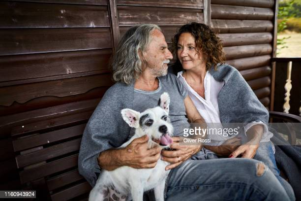 mature couple with dog sitting on porch of a log cabin - linda oliver fotografías e imágenes de stock