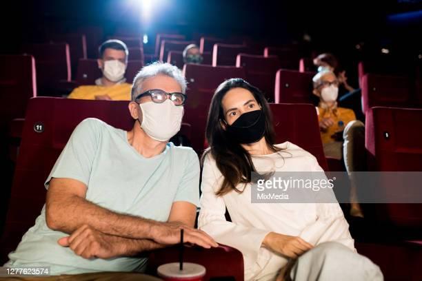 rijp paar met gezichtsmaskers die bij het bioscooptheater genieten - sneakpreview stockfoto's en -beelden