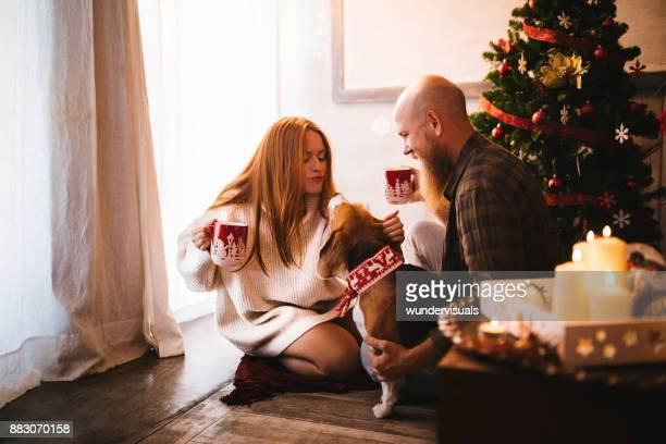 クリスマス ツリーの下にホット チョコレートふれあい犬と熟女のカップル