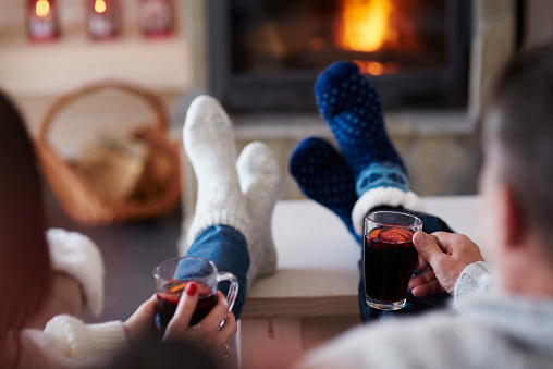 Mature couple with hot drinks in living room at the fireplace - gettyimageskorea