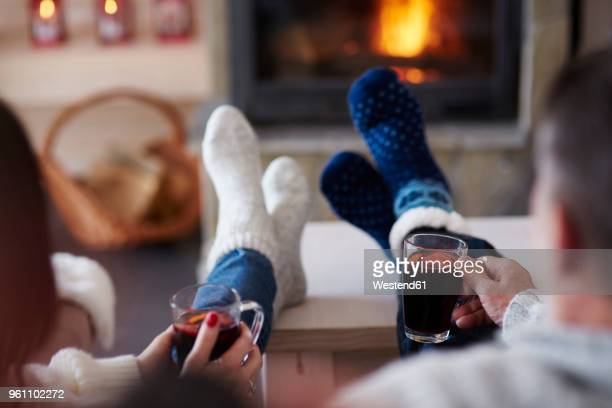 mature couple with hot drinks in living room at the fireplace - calientes fotografías e imágenes de stock