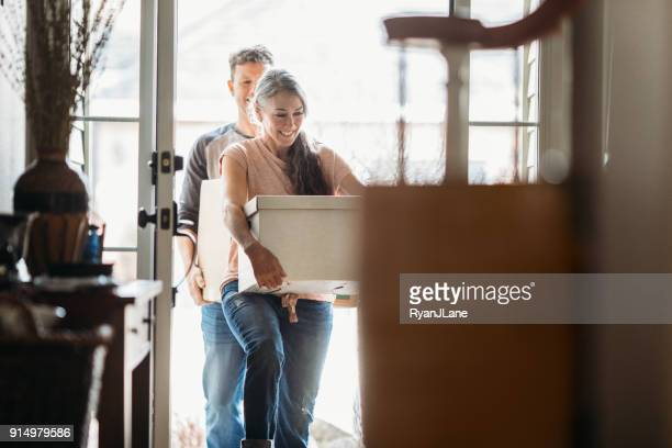 mature couple with moving boxes in new home - unpacking stock pictures, royalty-free photos & images