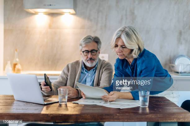 mature couple with papers and laptop on kitchen table at home - 55 59 jaar stockfoto's en -beelden