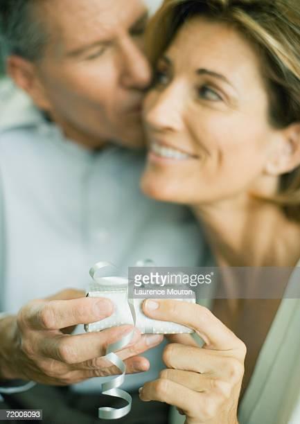 mature couple with present, man kissing woman's cheek - de amado carrillo fuentes fotografías e imágenes de stock