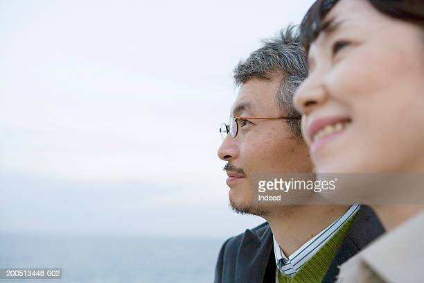 mature couple, with sea in background, close-up, side view - asian 50 to 55 years old woman stock photos and pictures
