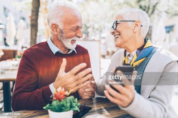 mature couple with smartphone - young at heart stock pictures, royalty-free photos & images