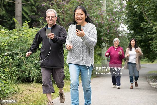 Mature Couple with Smartphones Run While Playing Augmented Reality Game