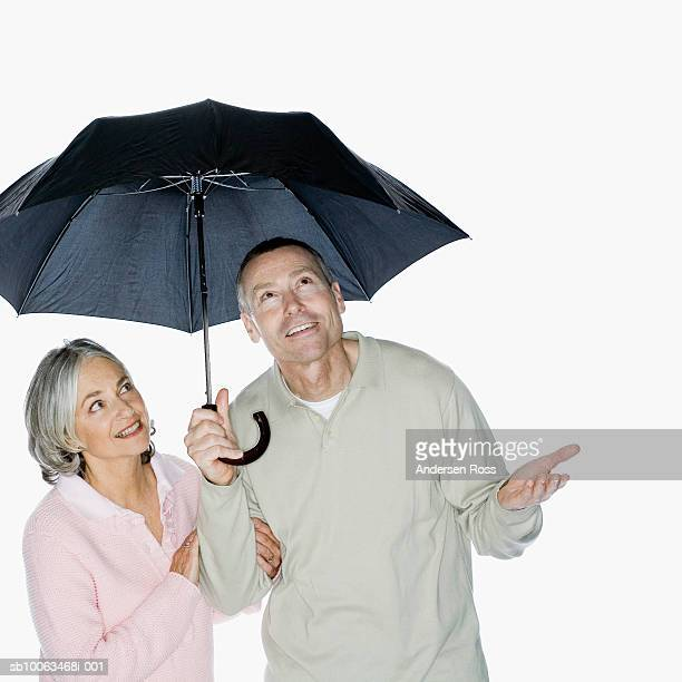 Mature couple with umbrella against white background