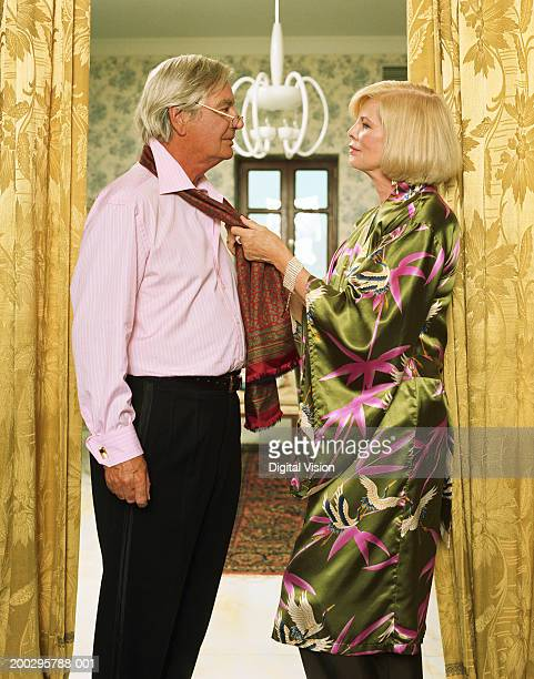 Mature couple woman pulling scarf around man's neck