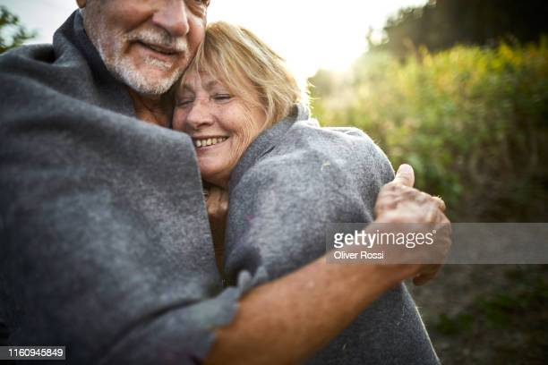 mature couple wrapped in a blanket cuddling in the countryside - 毛布 ストックフォトと画像