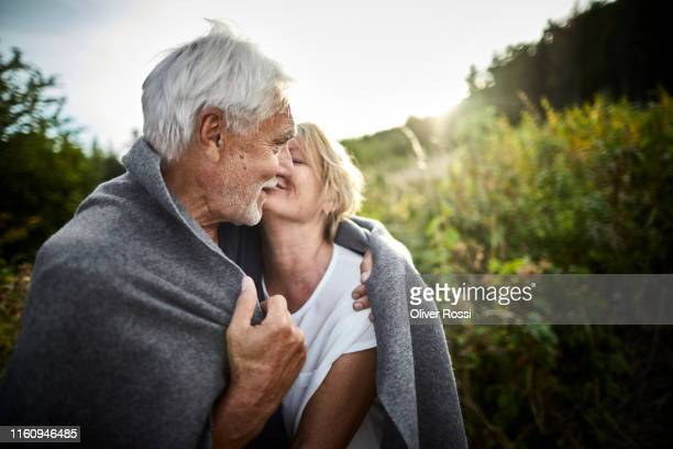 mature couple wrapped in a blanket cuddling in the countryside - love stock pictures, royalty-free photos & images