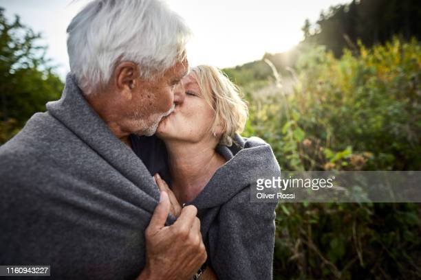 mature couple wrapped in a blanket kissing in the countryside - kiss stock pictures, royalty-free photos & images