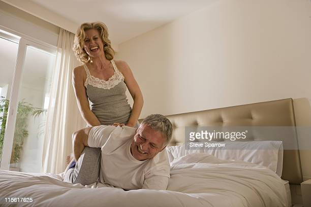 mature couple wrestling on bed - female wrestling holds stockfoto's en -beelden