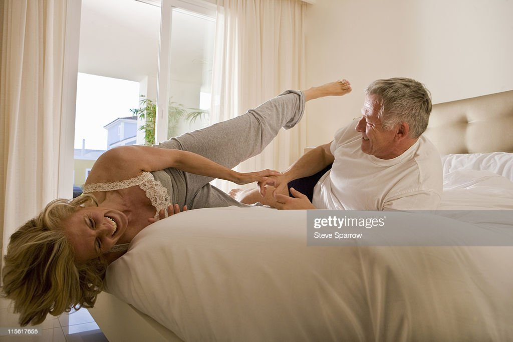 Mature couple wrestling on bed : Stock Photo