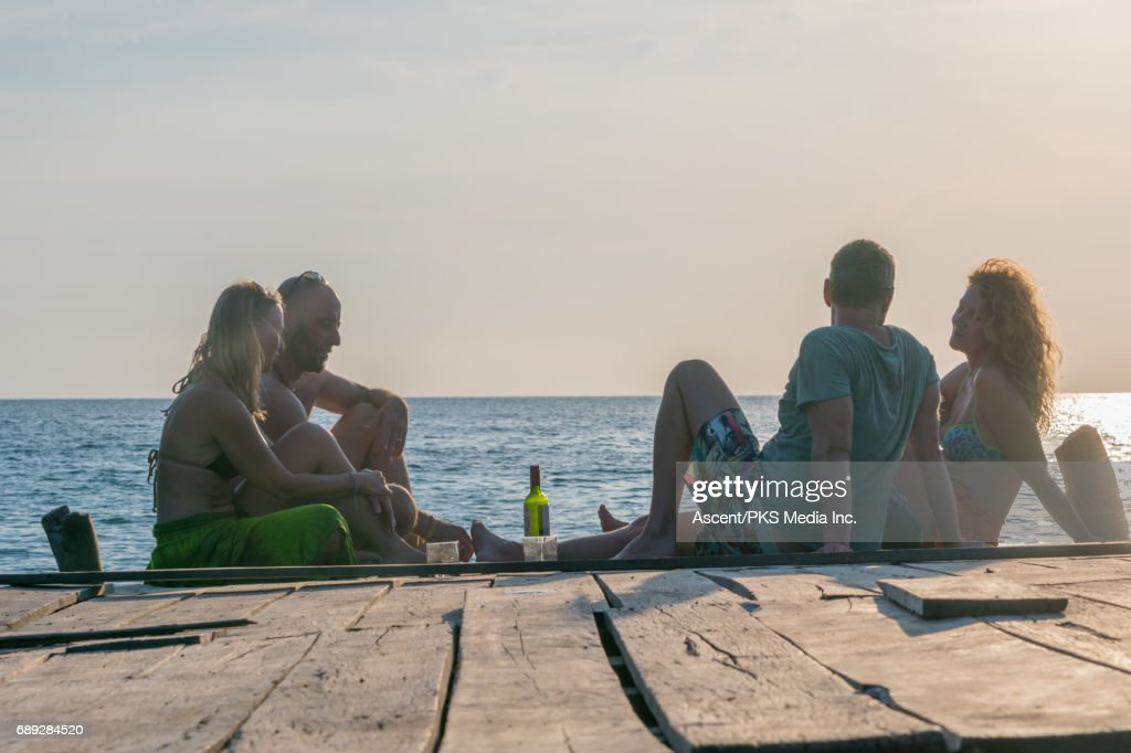 Mature couples enjoy wine on wooden deck at sunset : Stock Photo
