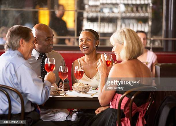 Mature couples having drinks in restaurant, smiling