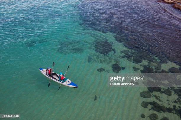 mature couple's kayak sea challenge (aerial photography). - israeli woman stock pictures, royalty-free photos & images