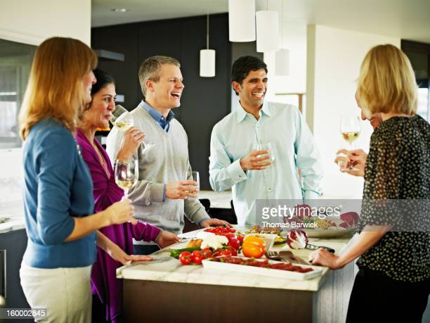 Mature couples preparing meal in home kitchen