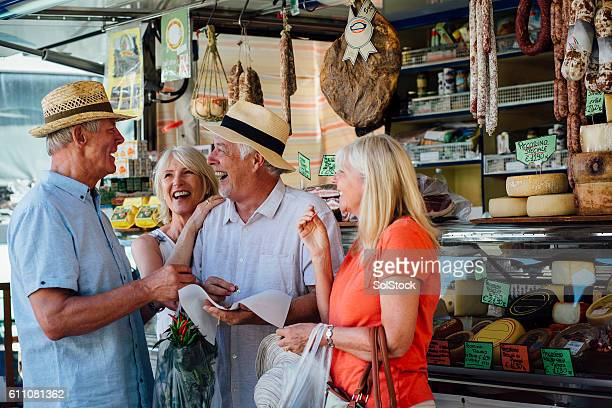 mature couples shopping in an italian delicatessen - markt stockfoto's en -beelden