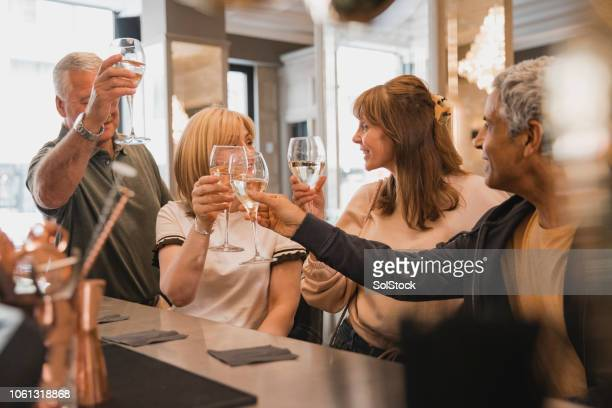 mature couples toasting at the bar - 50 59 years stock pictures, royalty-free photos & images