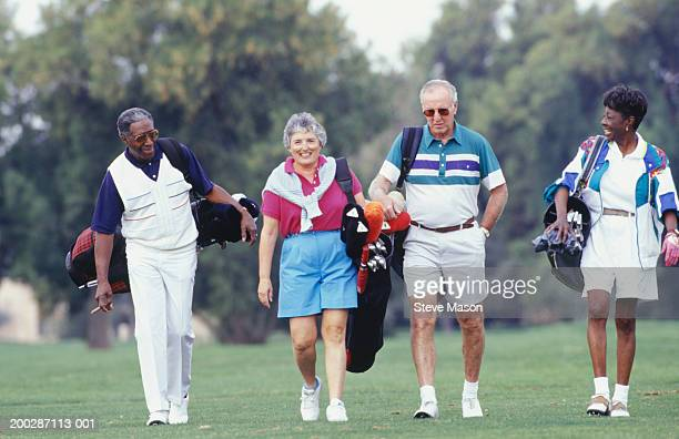 Mature couples walking on golf course