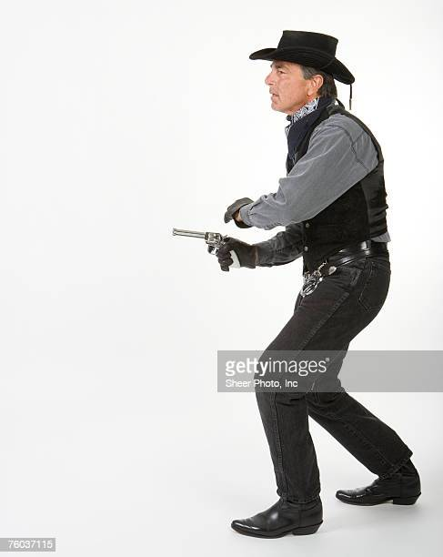 mature cowboy aiming gun, against white background, side view - studio shot stockfoto's en -beelden