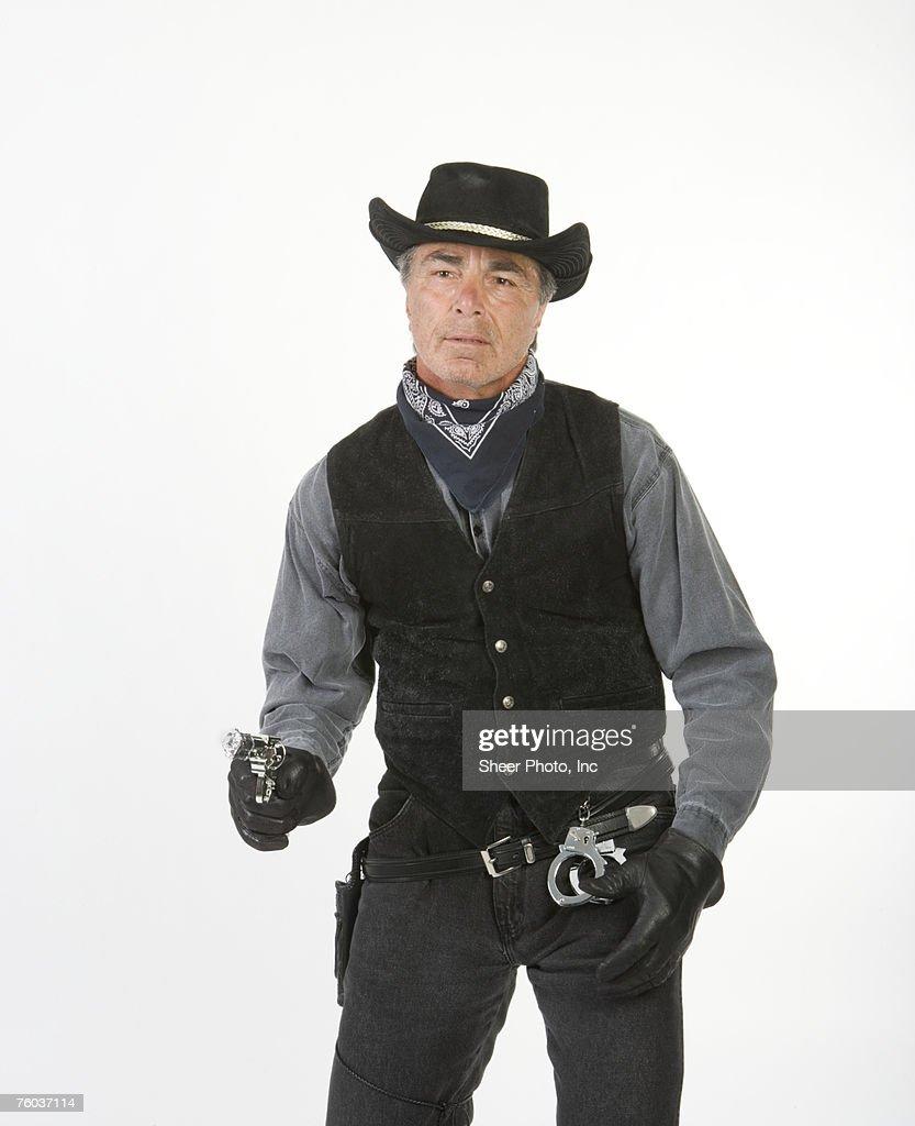 Mature Cowboy Holding Gun Against White Background Stock
