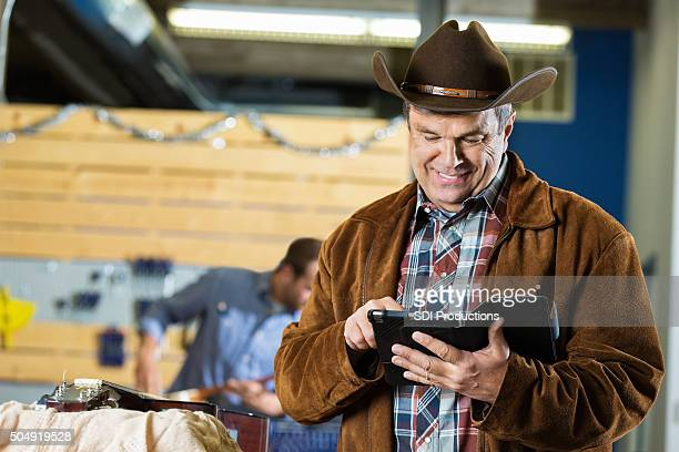 Mature cowboy using digital tablet while working on guitar