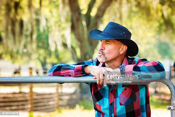 Mature cowboy whistling or calling his cattle
