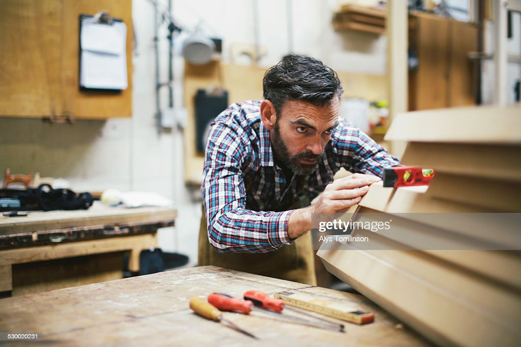 Mature craftsman using spirit level in pipe organ workshop : Stock Photo