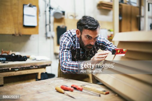 Mature craftsman using spirit level in pipe organ workshop