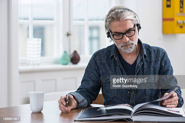 Mature creative man with headset reading book