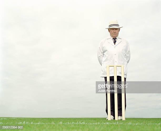 Mature cricket umpire behind wicket, portrait