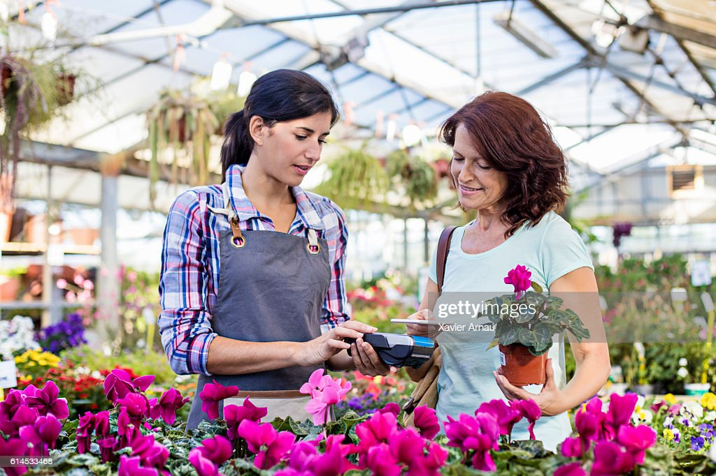 Mature customer making a contactless payment in garden center : Stock Photo