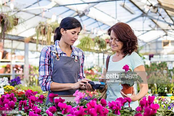 Mature customer making a contactless payment in garden center