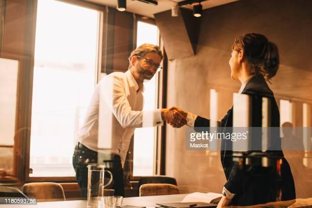mature customer shaking hands with female lawyer in meeting - advogado imagens e fotografias de stock