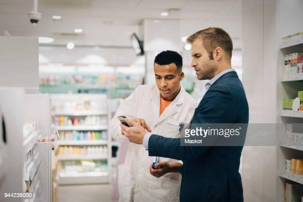 mature customer showing mobile phone to male pharmacist standing at medical store - pharmacy stock pictures, royalty-free photos & images
