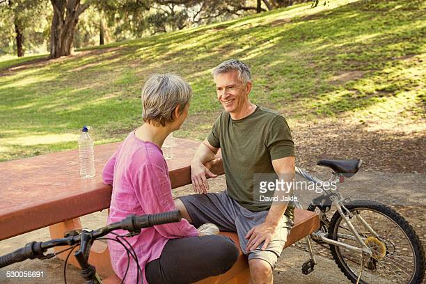 Mature cycling couple taking a break on park picnic table