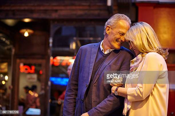 Mature dating couple sarm in arm on city street at night, London, UK